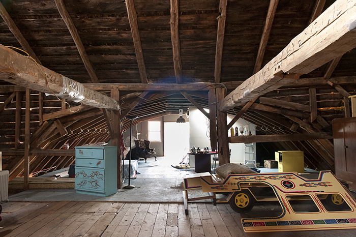 wide shot of the 2nd floor of the barn, scattered projects and furniture on the floor