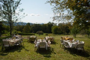 wide shot of empty set tables for the farm feast fundraiser, sunny field in front of catskill mountain range