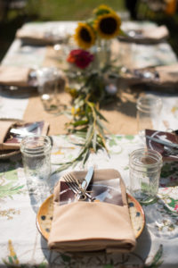 detail shot of silverware, thank you card, and napkin/plate on sun-dappled table