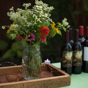 detail shot of wild and domestic flower arrangement on a tray, with bottles of wine nearby