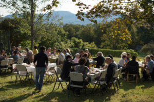 full tables at farm feast with sunny catskills in background