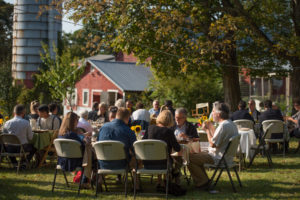 full sunny tables at farm feast with backdrop of FAEx barn