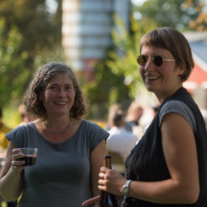 Asia Sosniewski and Kristie Gibson, smiling, looking at camera, and drinking wine