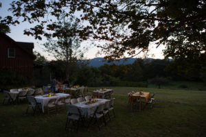 emptied tables at dusk with tealights and dimming catskill mountain range as backdrop