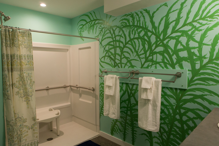 shot of 1st floor ADA bathroom with towel rack, roll-in shower, and shower chair